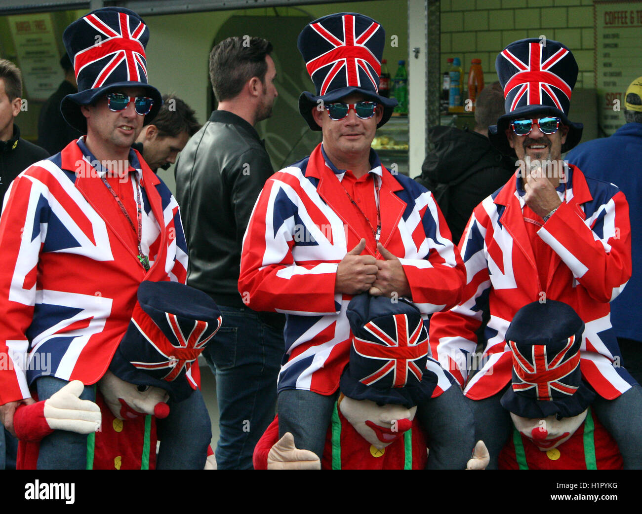 Three British Fans Supporting Great Britain Team Competition in their Union Jack Fancy Dress and Top Hats - Stock Image