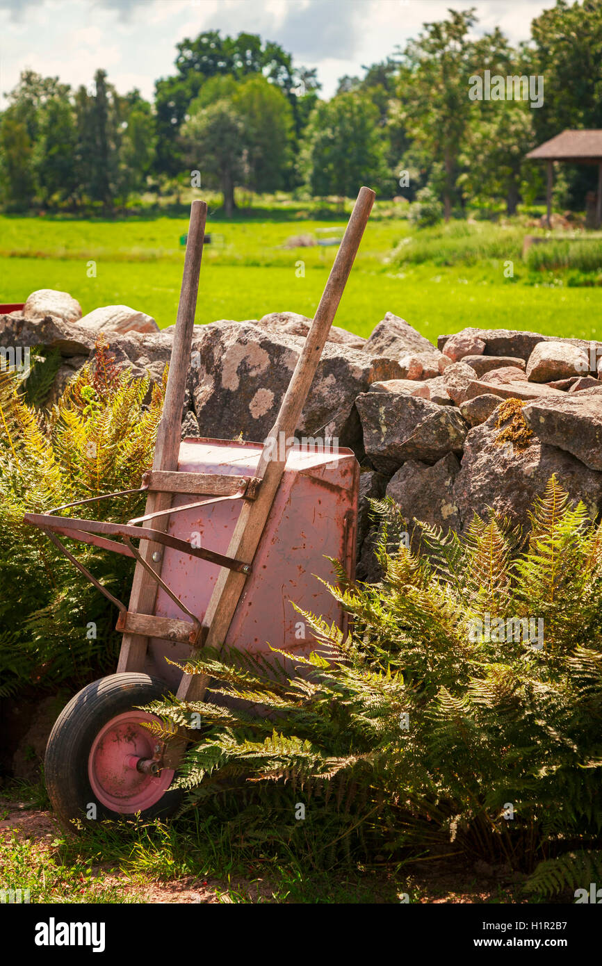 Image of a wheelbarrow against a natural stone wall in a rural setting. - Stock Image
