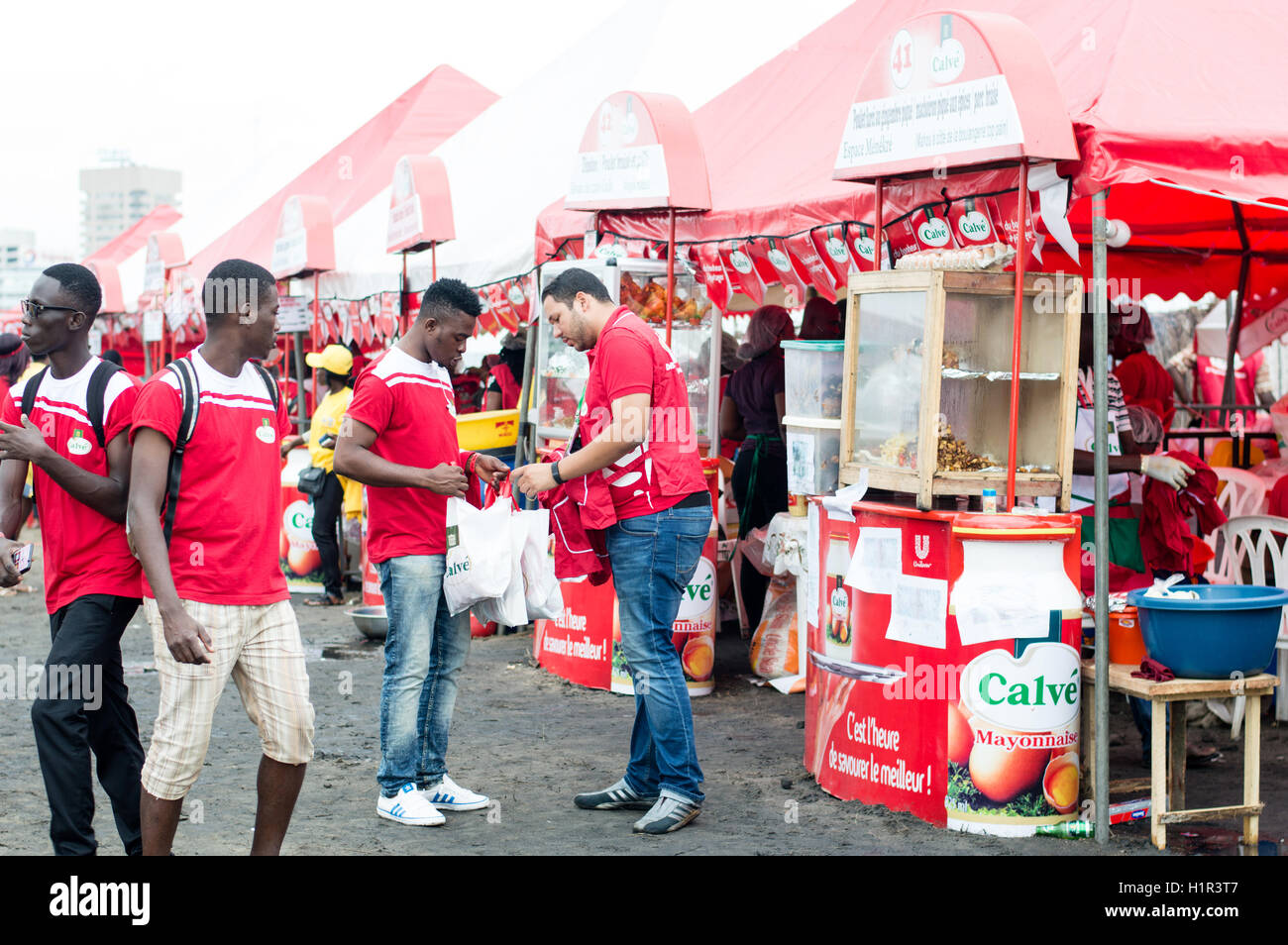 -Abidjan, Ivory Coast, September 11, 2016: Festival of Abidjan grilled with red decorations and sponsors color . - Stock Image