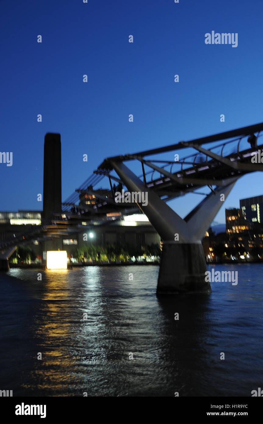 A vertical shot of London's Millennium Bridge, at night. - Stock Image