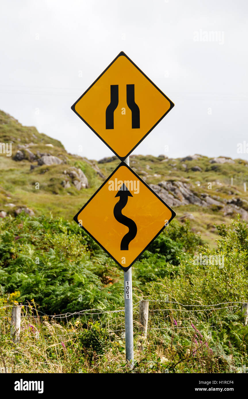Signs of winding road and bottleneck on a Irish road - Stock Image