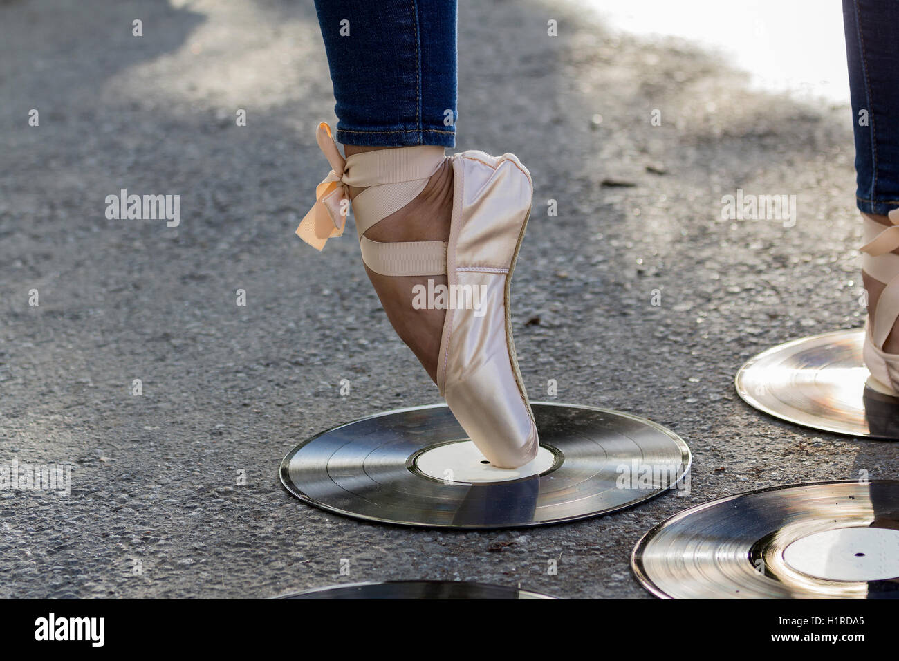 Feet girl in Ballet shoes stand amid vinyl discs. - Stock Image