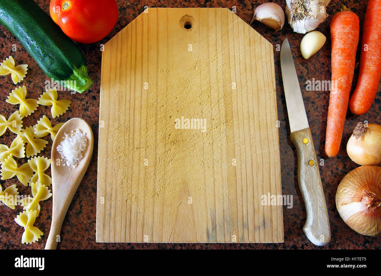 Top view of a clean cutting plank surrounded of food ingredients and kitchen utensils - Stock Image