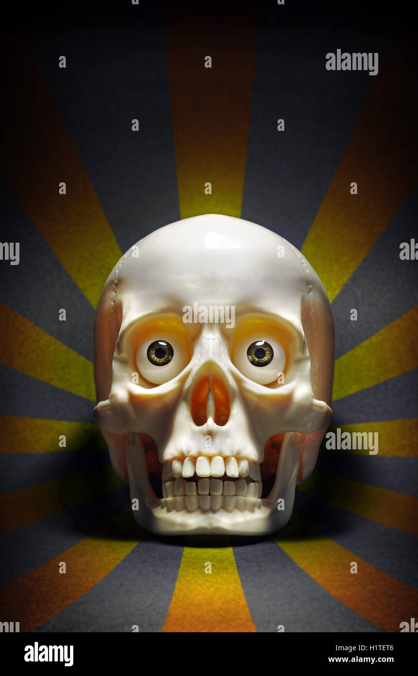 scary human skull with eyes staring, over a dark background with yellow stripes - Stock Image
