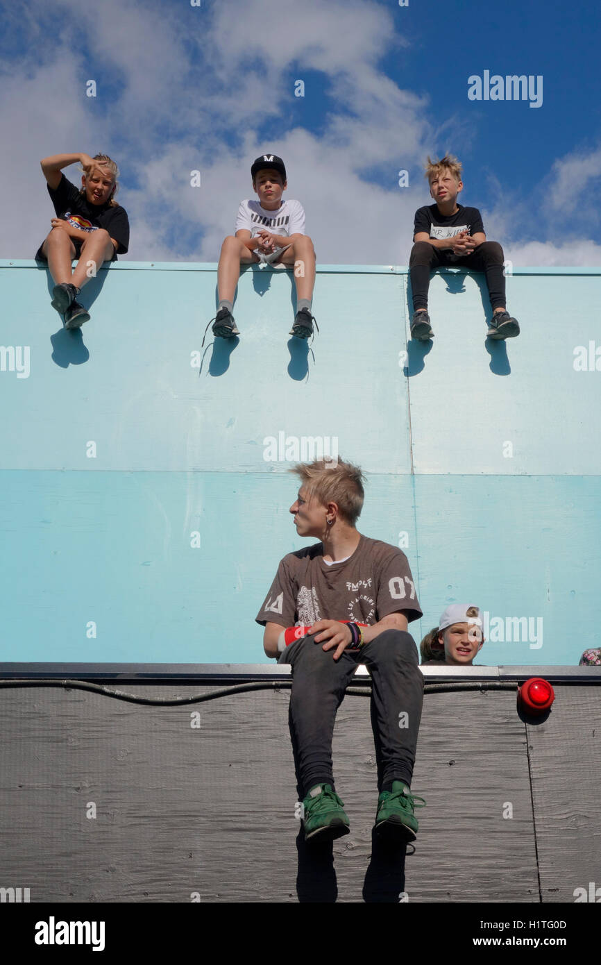 Parkour kids sit and relax on a edge of a building's terrace. - Stock Image