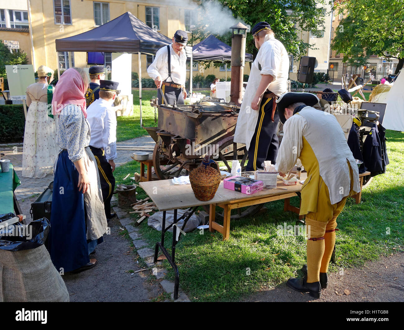 Swedish Caroleans (17th century) re-enactment scene. Military men prepare and serve food on a wood burning stove - Stock Image