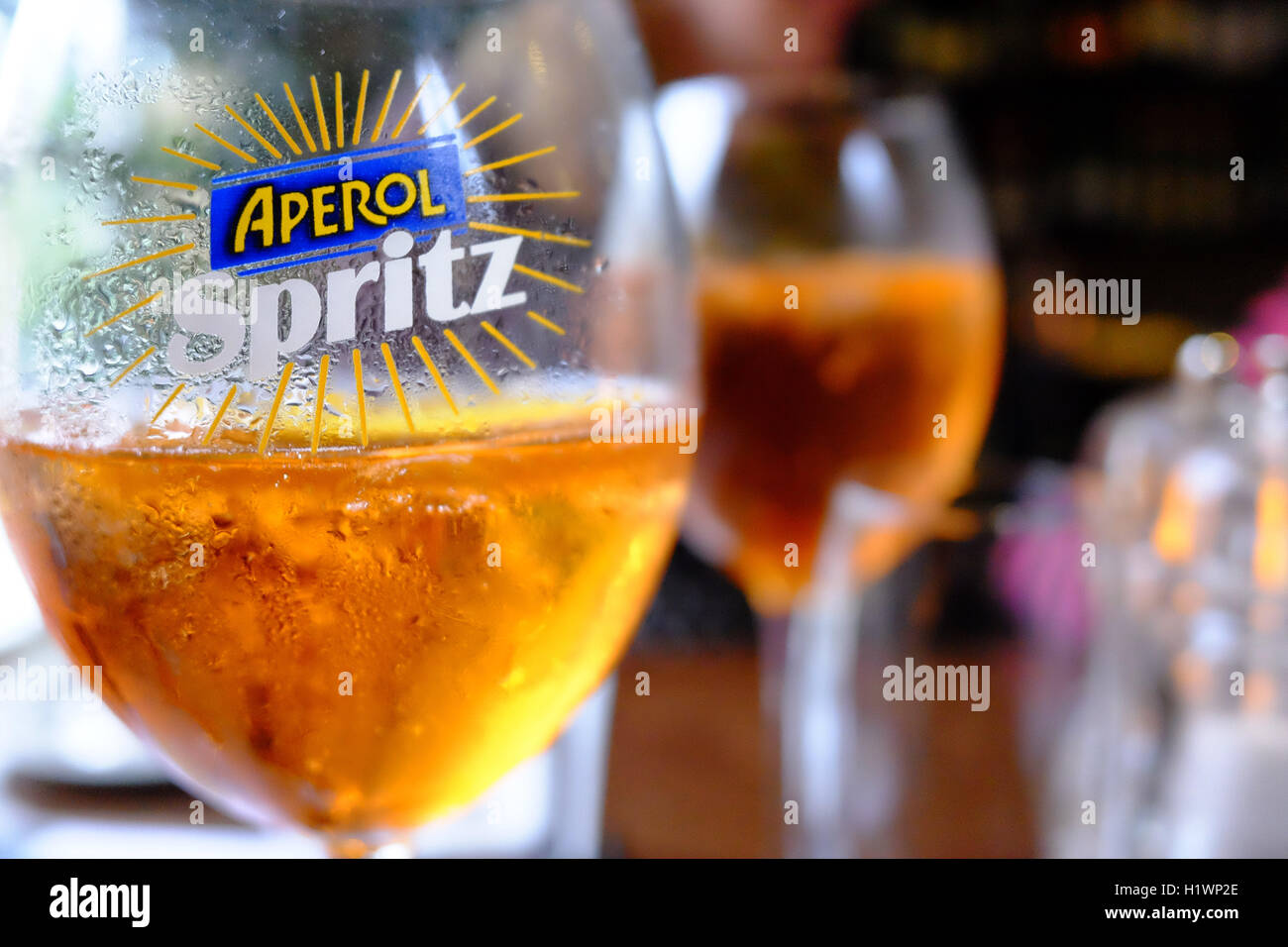 Two glasses of Aperol Spritz with ice in labeled glasses on a table - Stock Image