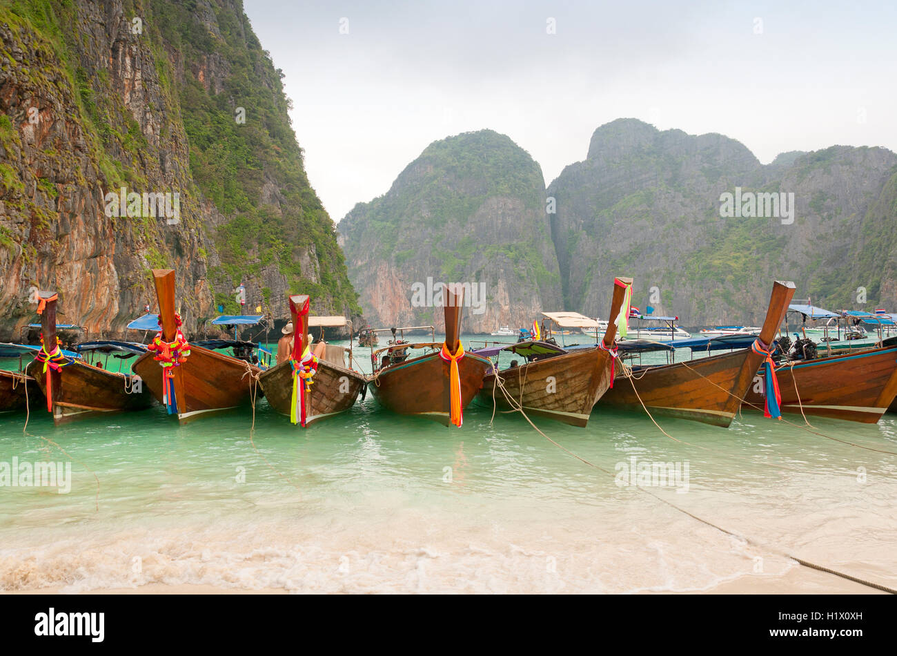 Boats lined up on Maya Bay located on Phi Phi Ley Island in Andaman Sea Thailand on Christmas day in the tropics. - Stock Image