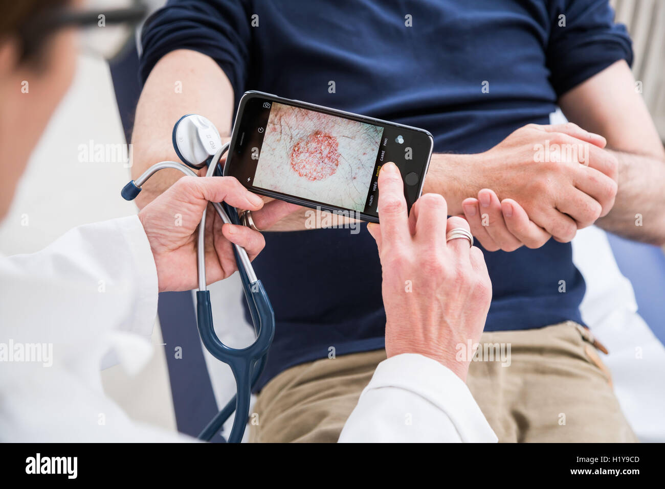 Doctor using his phone to transfer medical data. - Stock Image