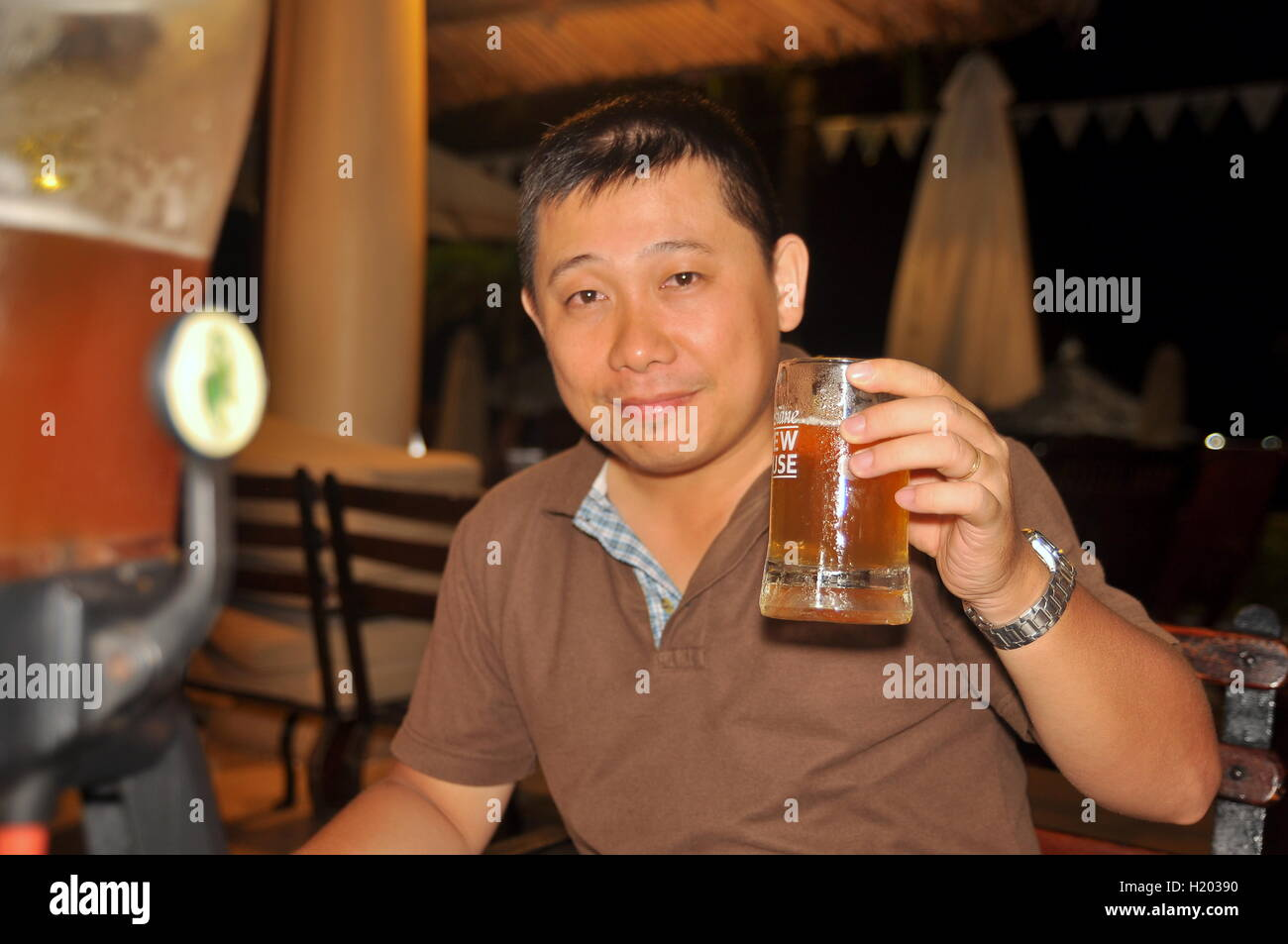 Nha Trang, Vietnam - July 11, 2015: A man is enjoying his glass of cold special beer at the Lousiana brew house - Stock Image