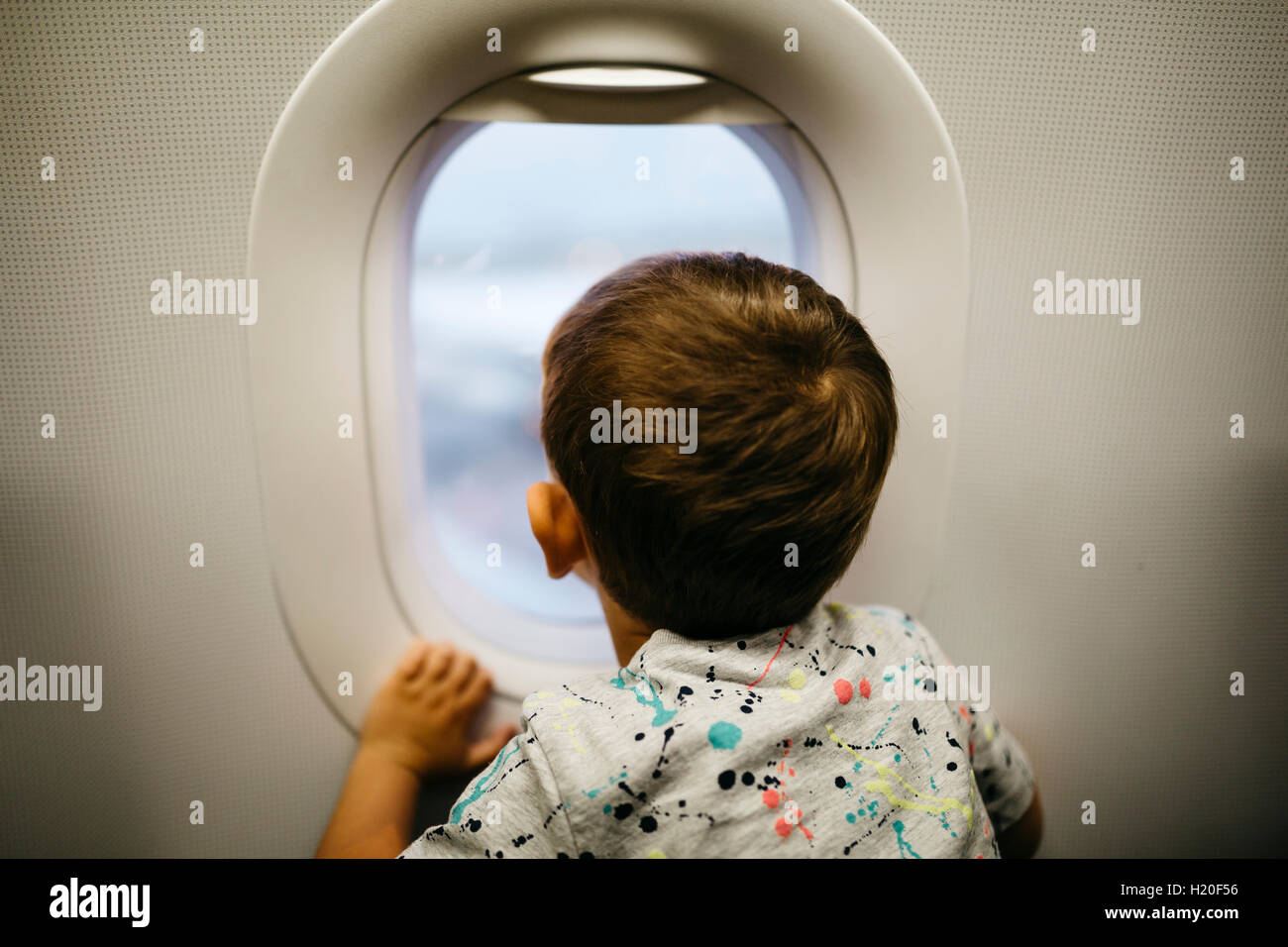 Little boy looking out of airplane window - Stock Image