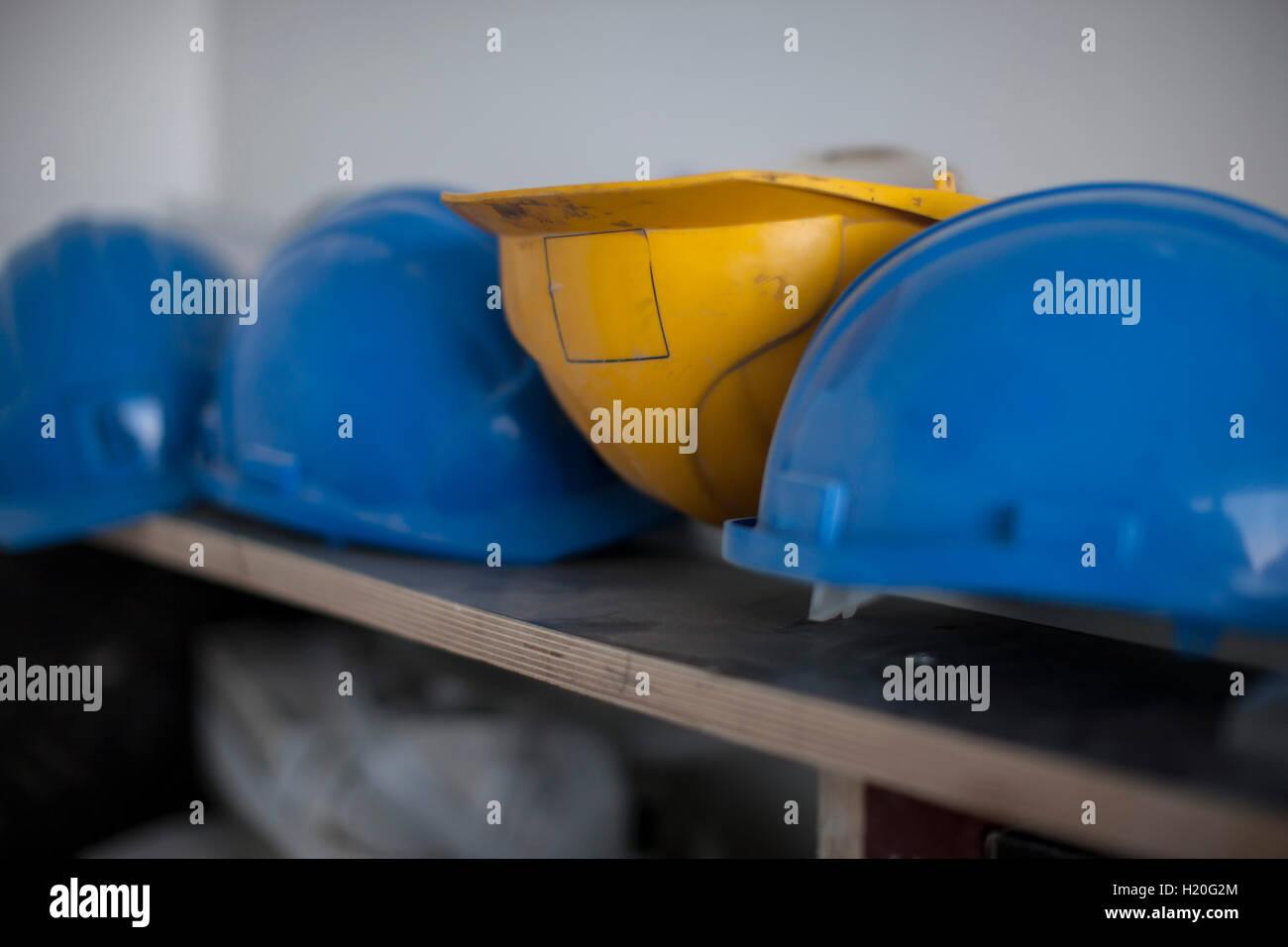 Hardhats on shelf - Stock Image