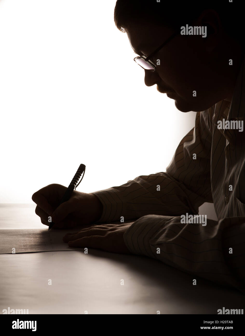 silhouette man is  writting on a sheet of paper - Stock Image