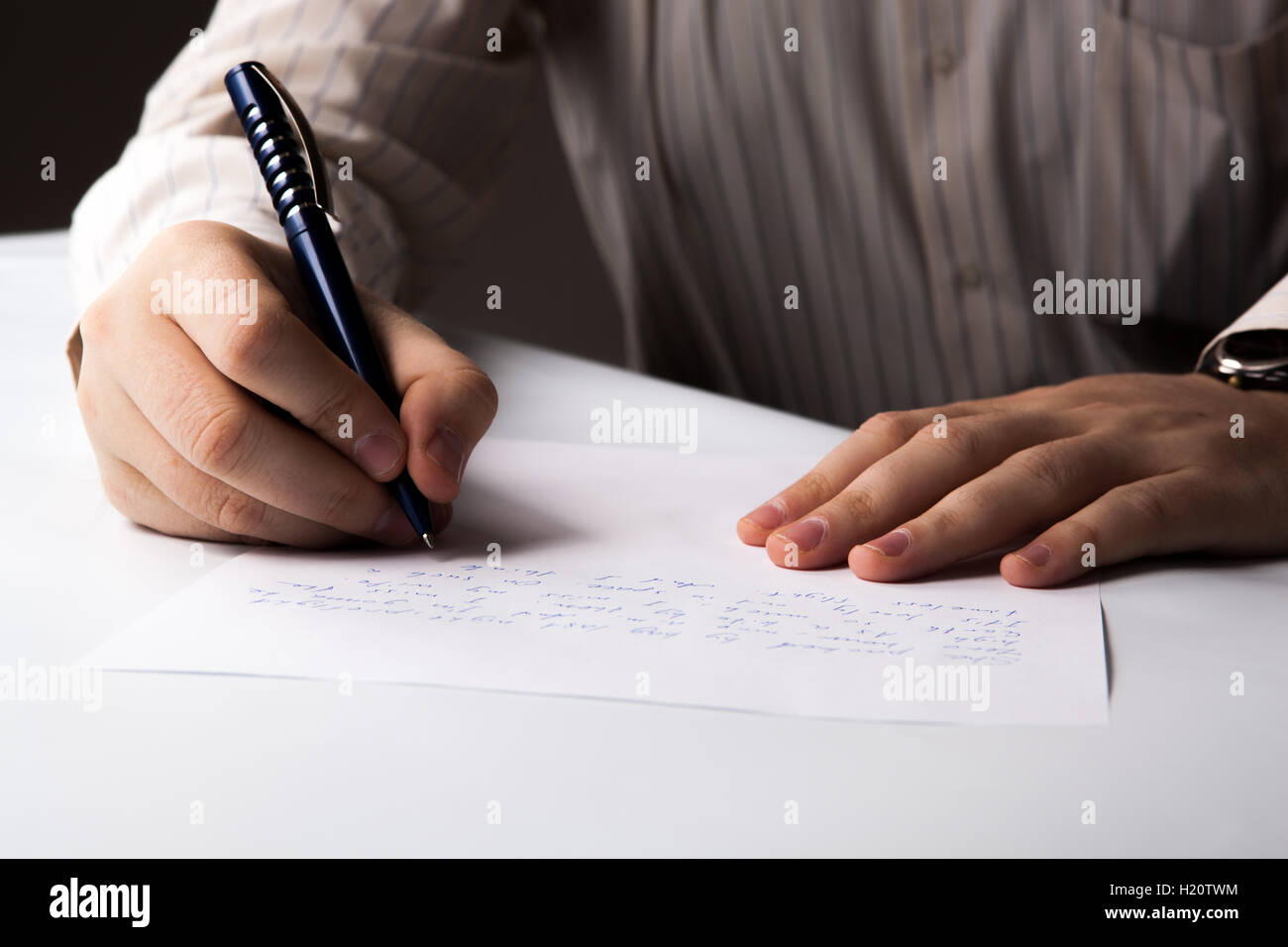man is  writting on a sheet of paper - Stock Image