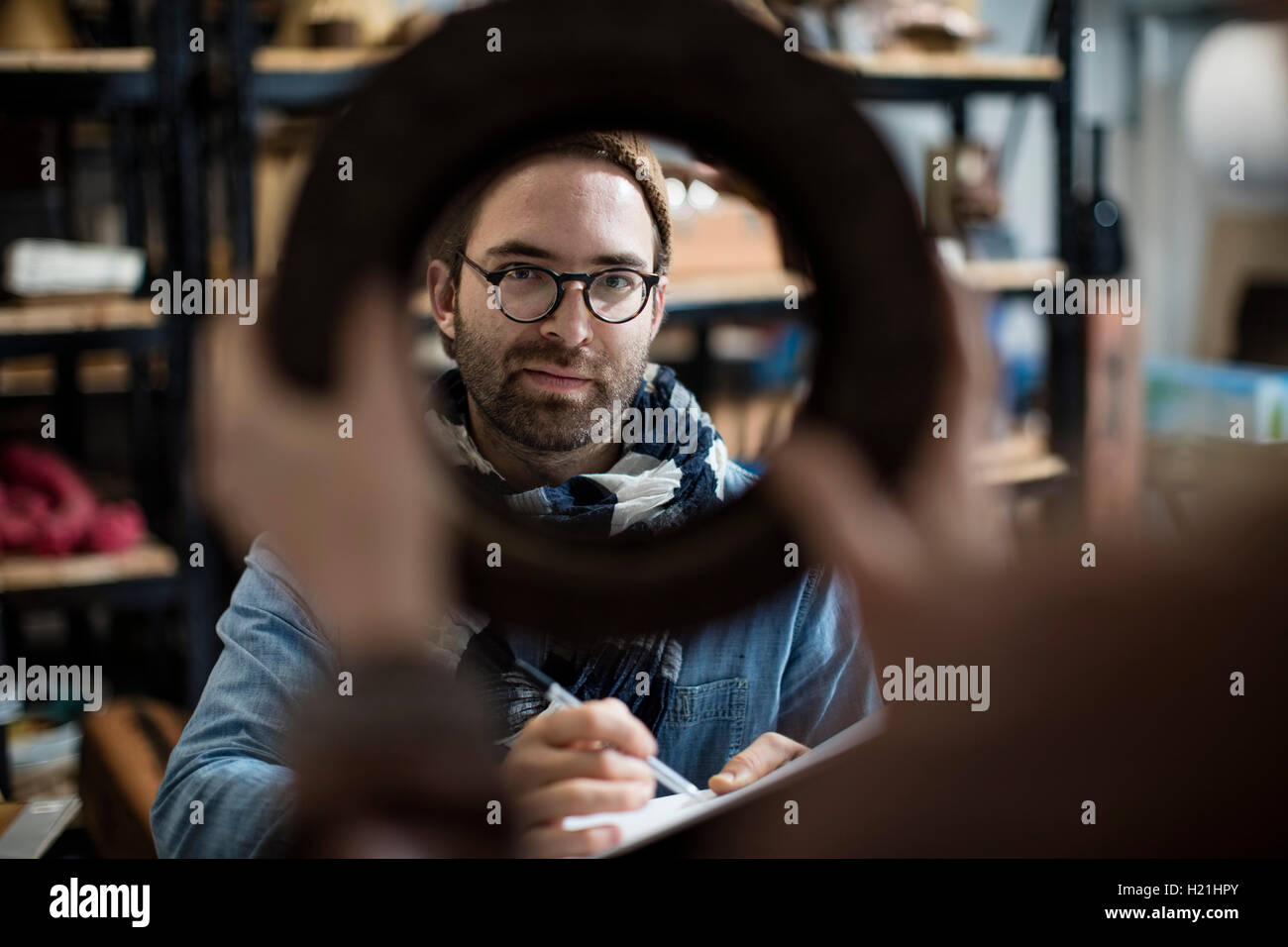 Man with sketchblock looking at sample held by colleague - Stock Image