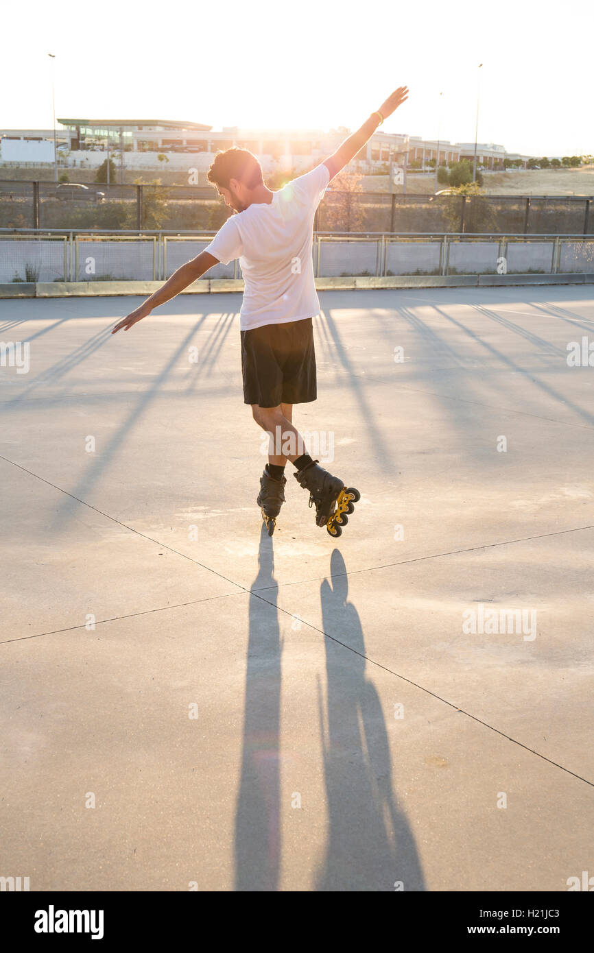 Man with rollerblades and arms extended at sunset - Stock Image