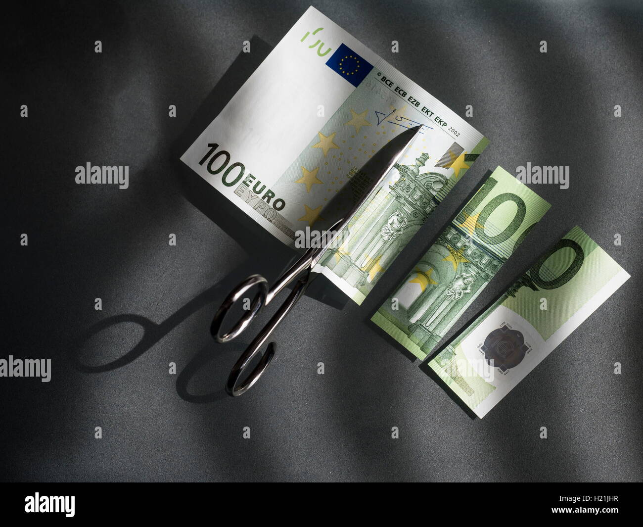 100 euro and scissors, symbolic picture, costs - Stock Image