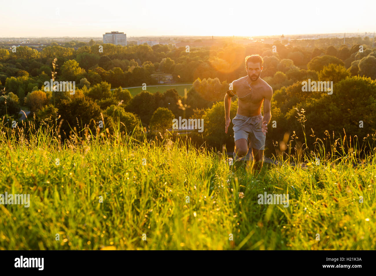 Barechested man running on meadow in park at sunset - Stock Image