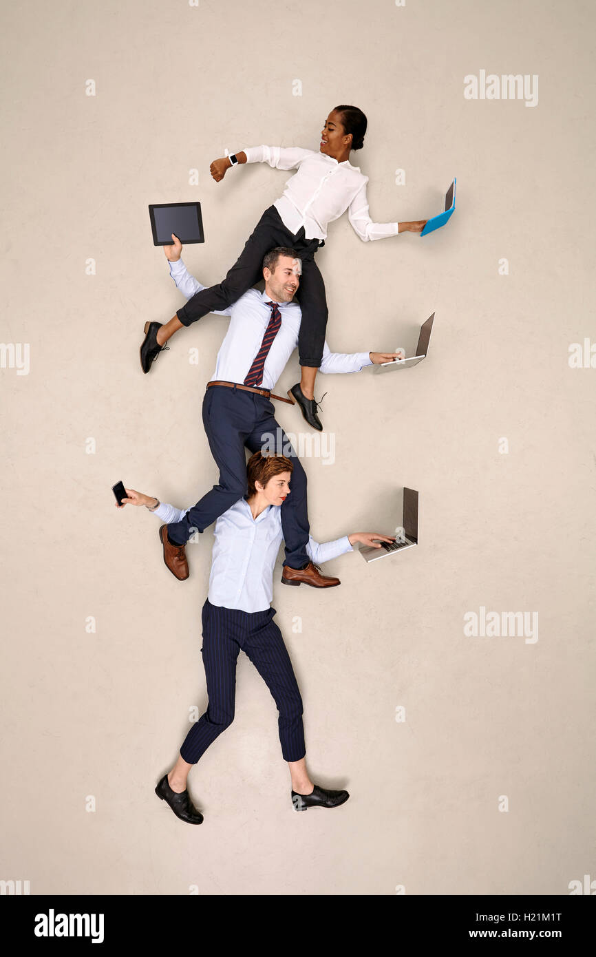 Businesswoman carrying colleagues on shoulders while working on mobile devices - Stock Image