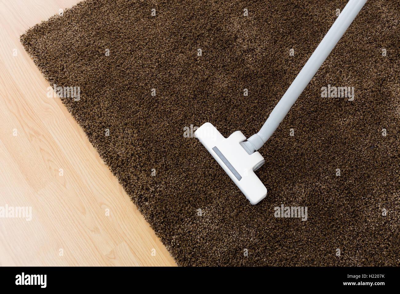 Head of modern vacuum cleaner on carpet - Stock Image