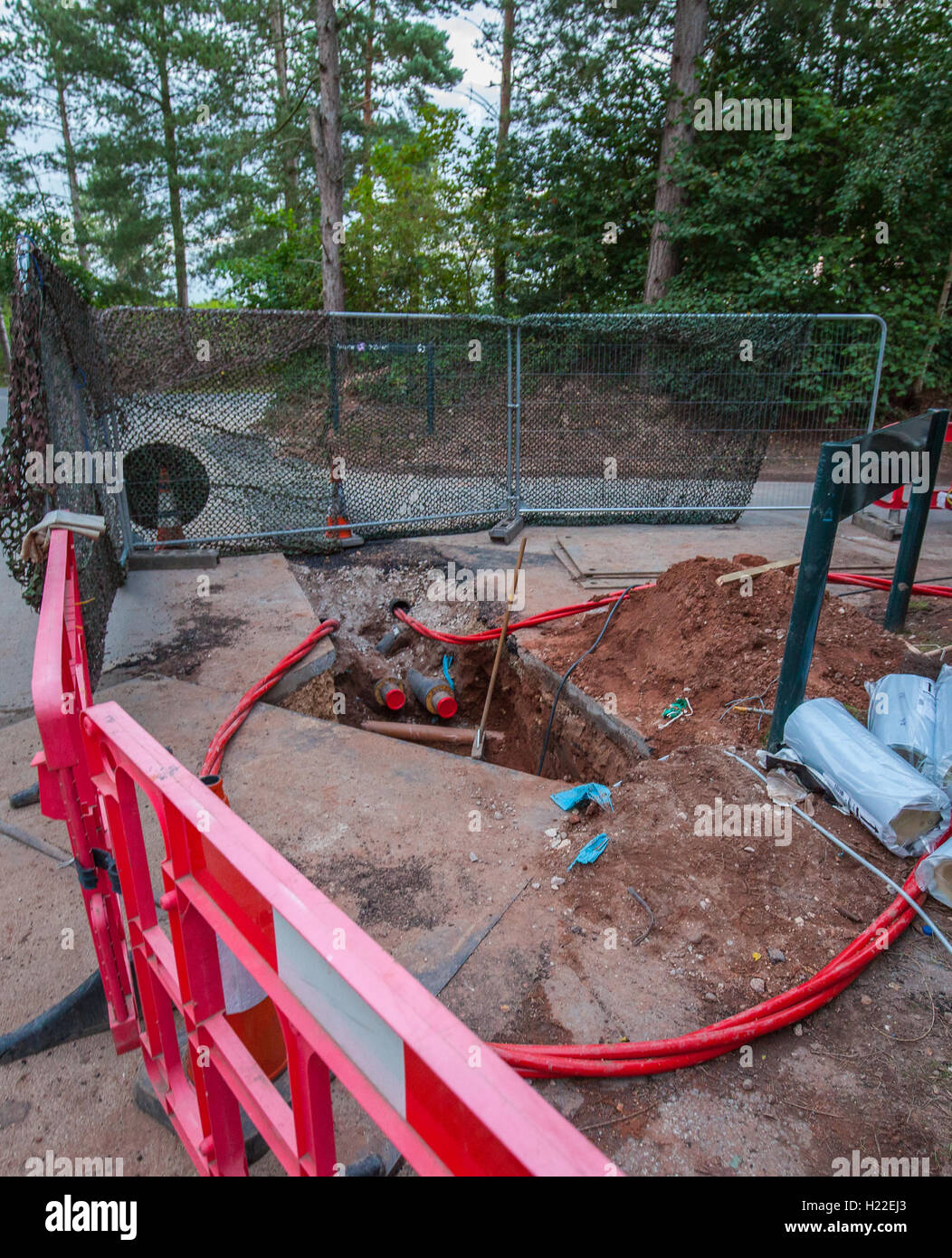 A hole being dug in the ground for utilities - Stock Image
