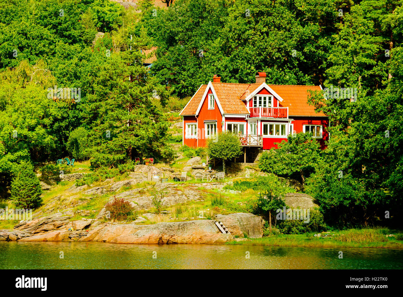 Askeron, Sweden - September 9, 2016: Environmental documentary of seaside home in woodland slope down to water. Stock Photo