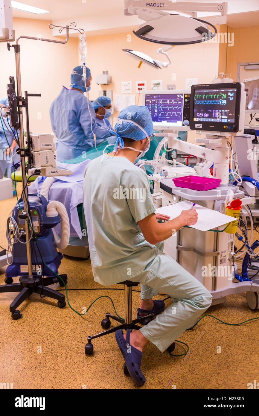 Surgical monitors being used to track the vital signs of a patient during an operation, Limoges hospital, France. - Stock Image