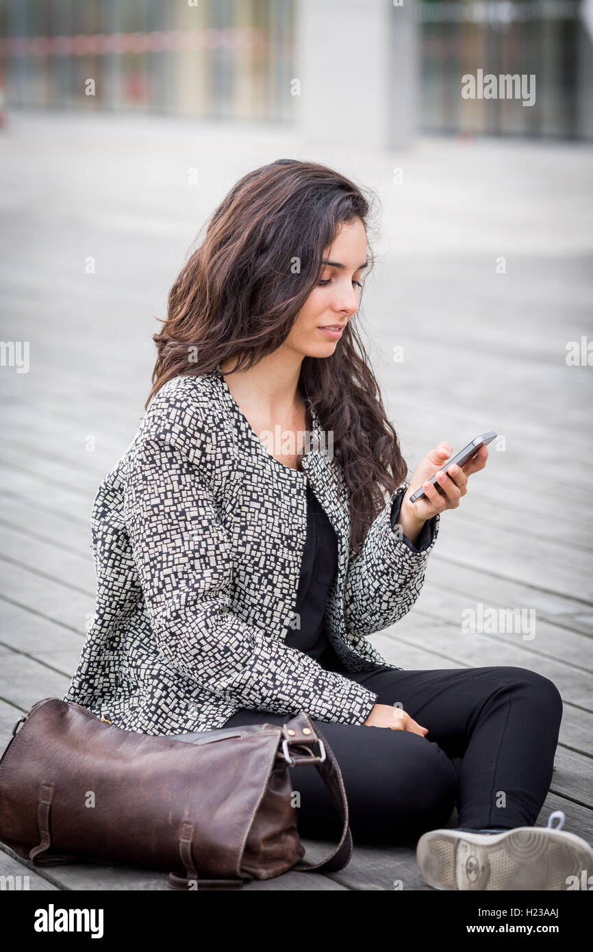 Woman using an Iphone. - Stock Image
