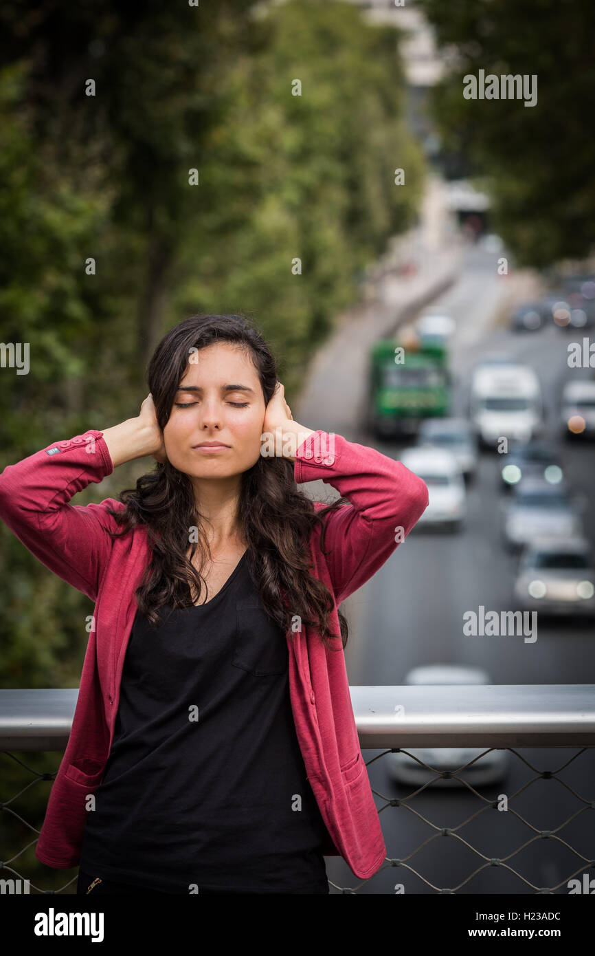 Woman annoyed by traffic noise - Stock Image