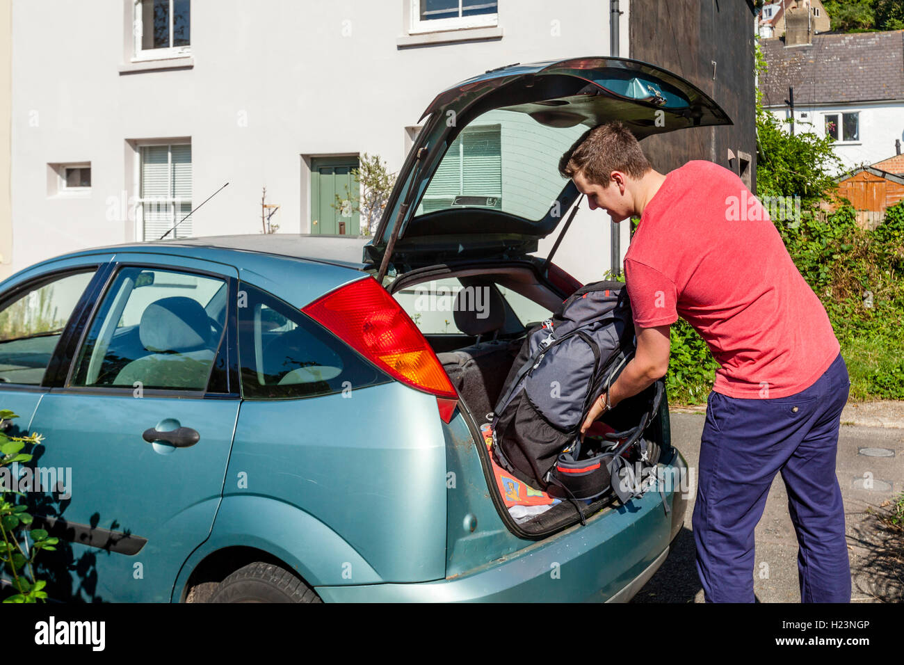 A Young Man Puts His Backpack Into A Car To Go Travelling, Sussex, UK - Stock Image