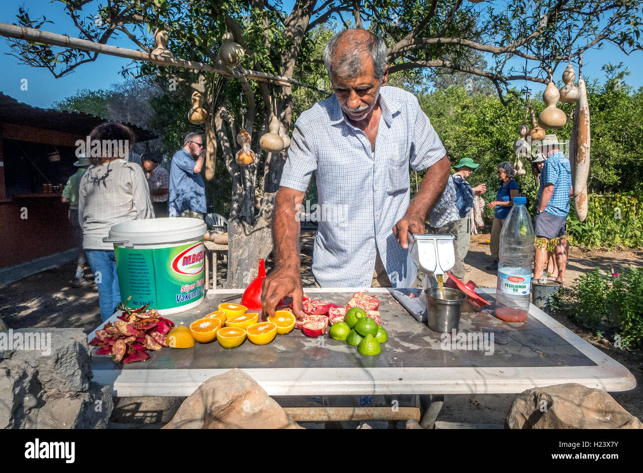 A man making freshly-squeezed fruit juice with oranges and pomegranates in northern Cyprus - Stock Image