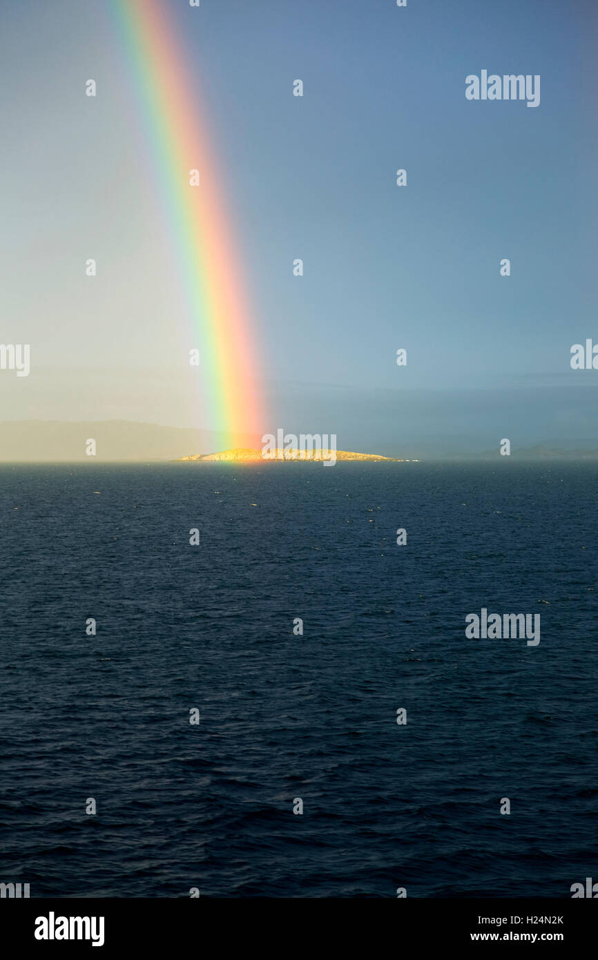 Seascape view of spectrum colours in rainbow over sea and island, Norway - Stock Image