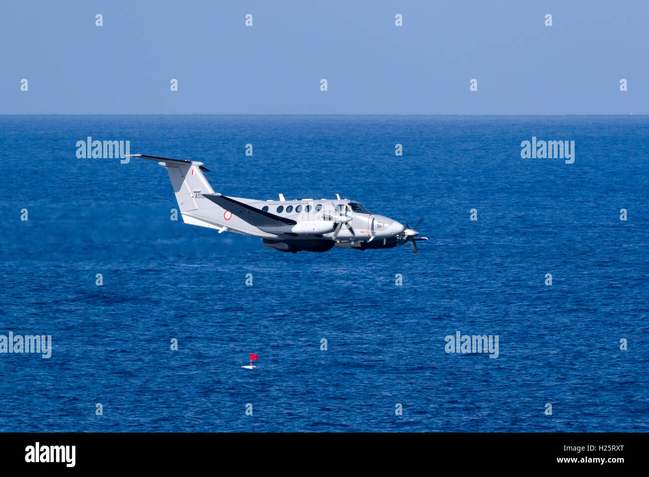 Malta Armed Forces Hawker Beechcraft B200 King Air [AS1227] performing a low pass over the sea. - Stock Image