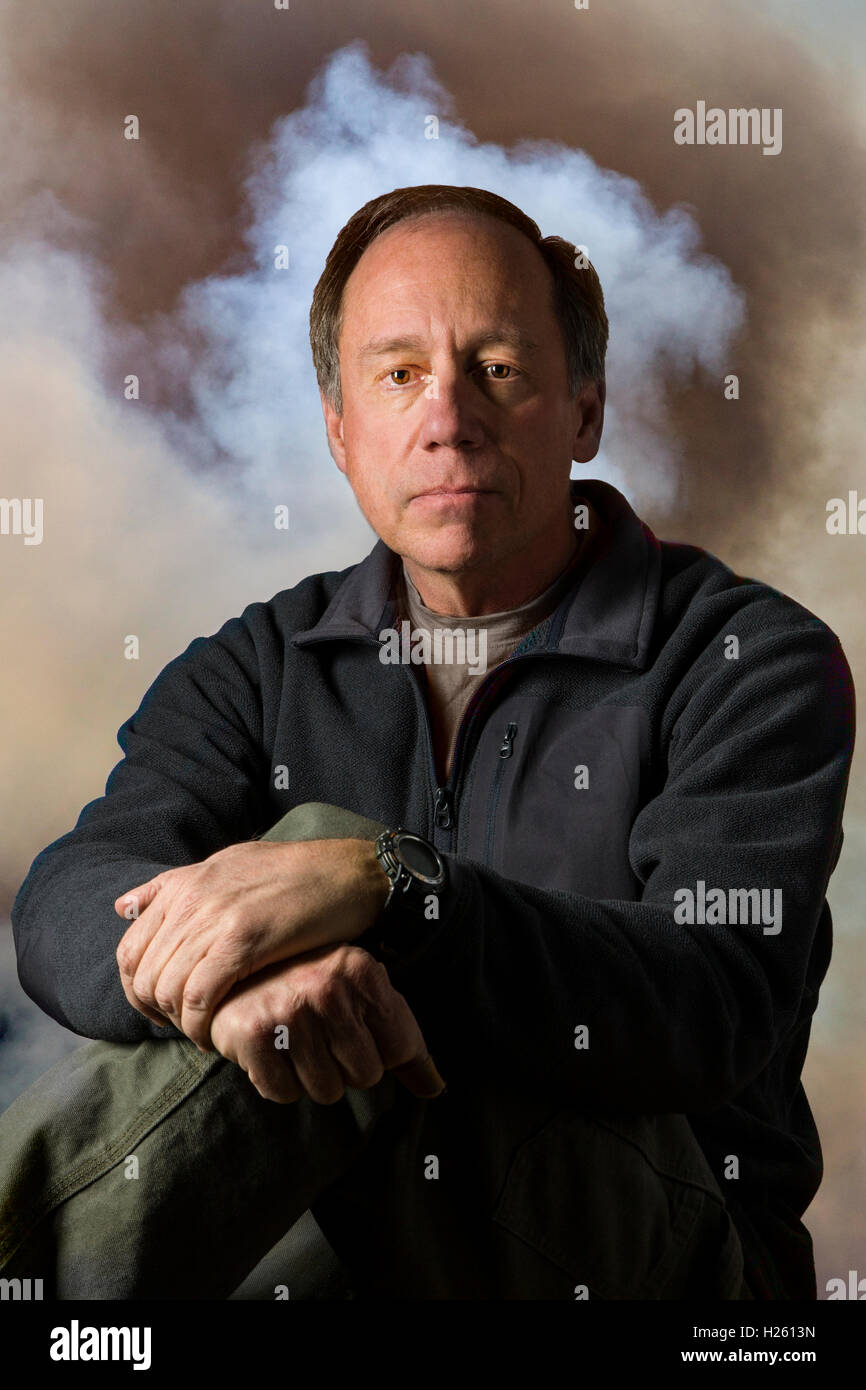 Mysterious smoky studio portrait of middle aged man - Stock Image