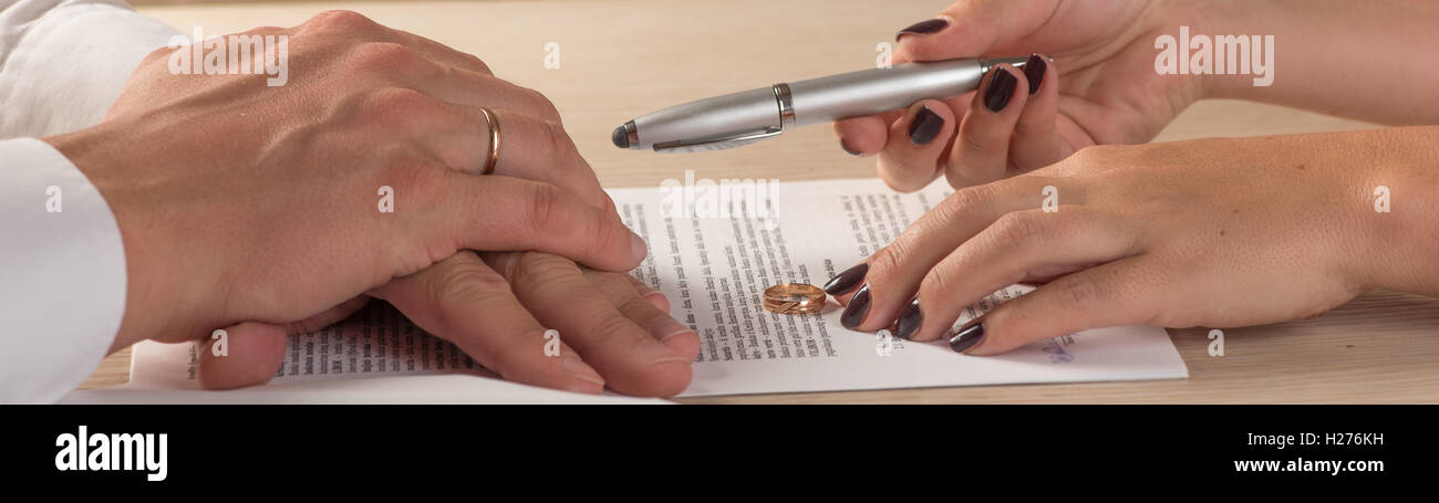 Wife and husband signing divorce documents or premarital agreement - Stock Image
