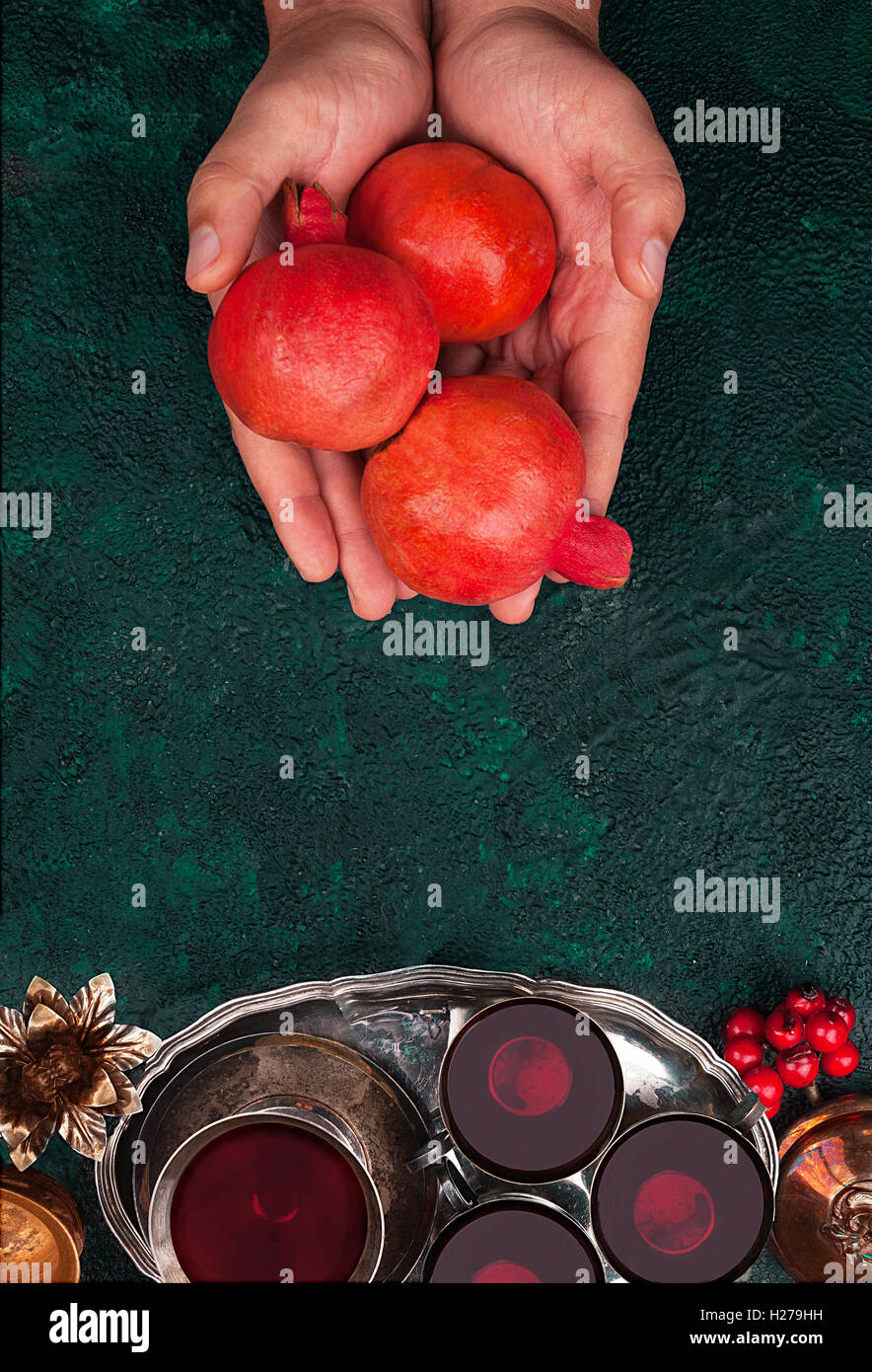 Man's hand with a pomegranate and pomegranate juice on textural background top view with copy space - Stock Image
