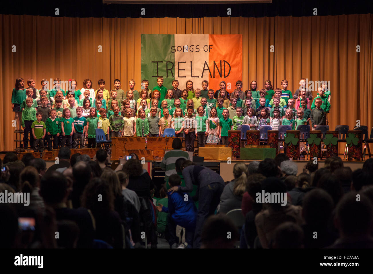 Large group of children singing songs of Ireland at a school performance on stage. St Paul Minnesota MN USA - Stock Image