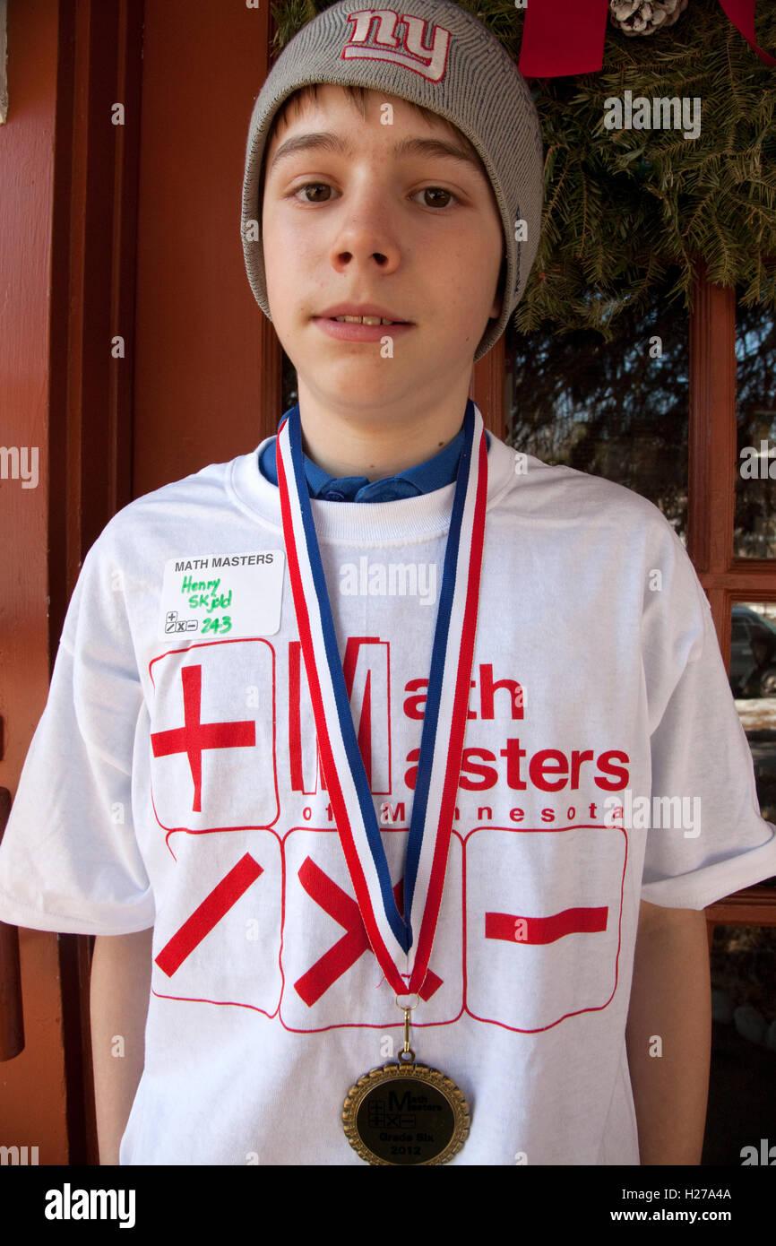 Boy age 12 wearing his Math Masters T-shirt and award medallion St Paul Minnesota MN USA - Stock Image