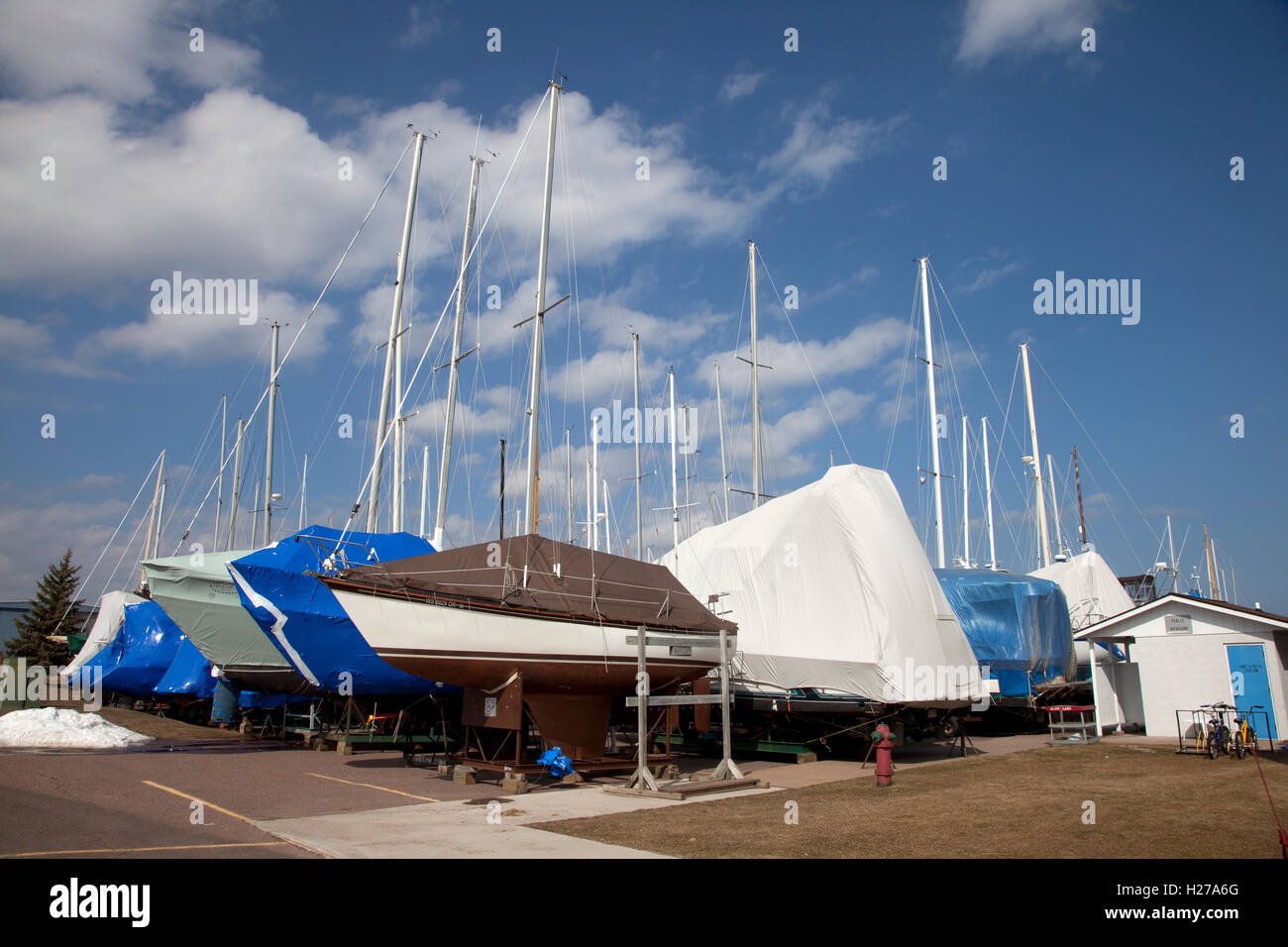 Cluster of sailboats and yachts wrapped for winter storage on land at The Washburn Marina. Washburn Wisconsin WI - Stock Image