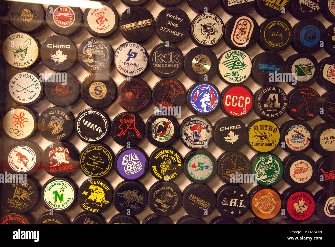 Array collection of team and tournament hockey pucks on display at ...