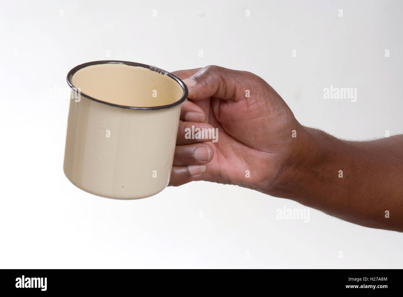 African's hand holding an empty enameled tin mug, could be begging or asking for drink or food - Stock Image