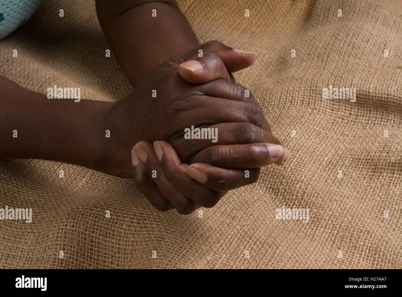 African's hands clasped in prayer or repose - Stock Image