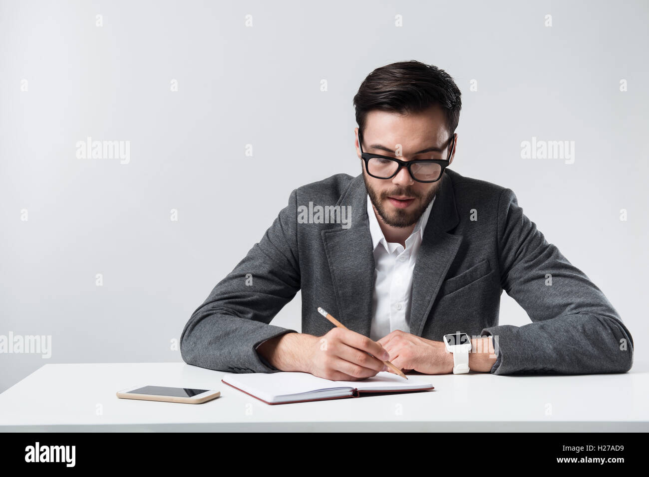Serious bearded man making notes. Stock Photo