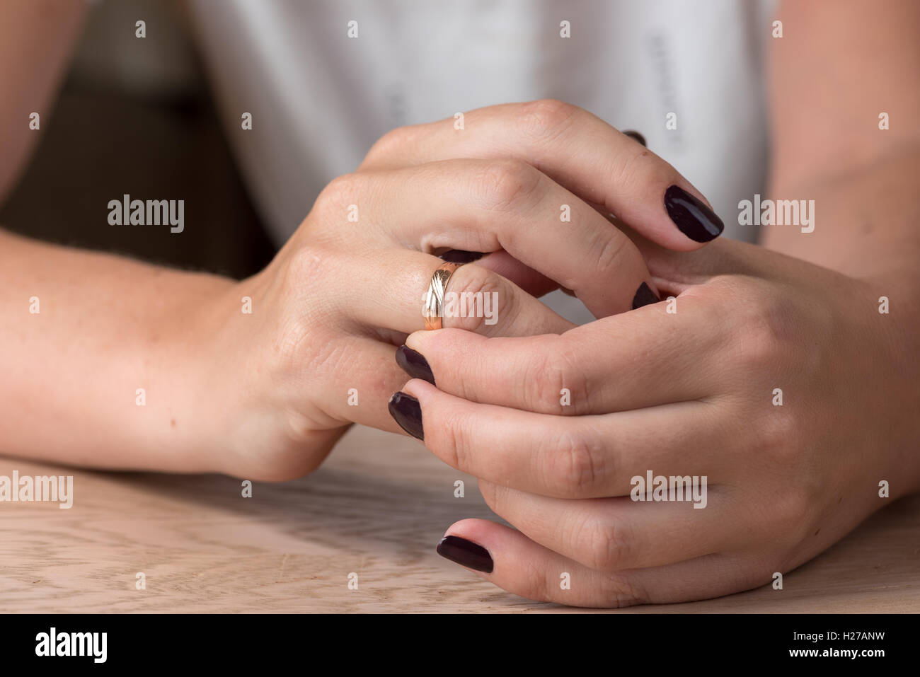 Divorce, separation: woman removing wedding or engagement ring - Stock Image
