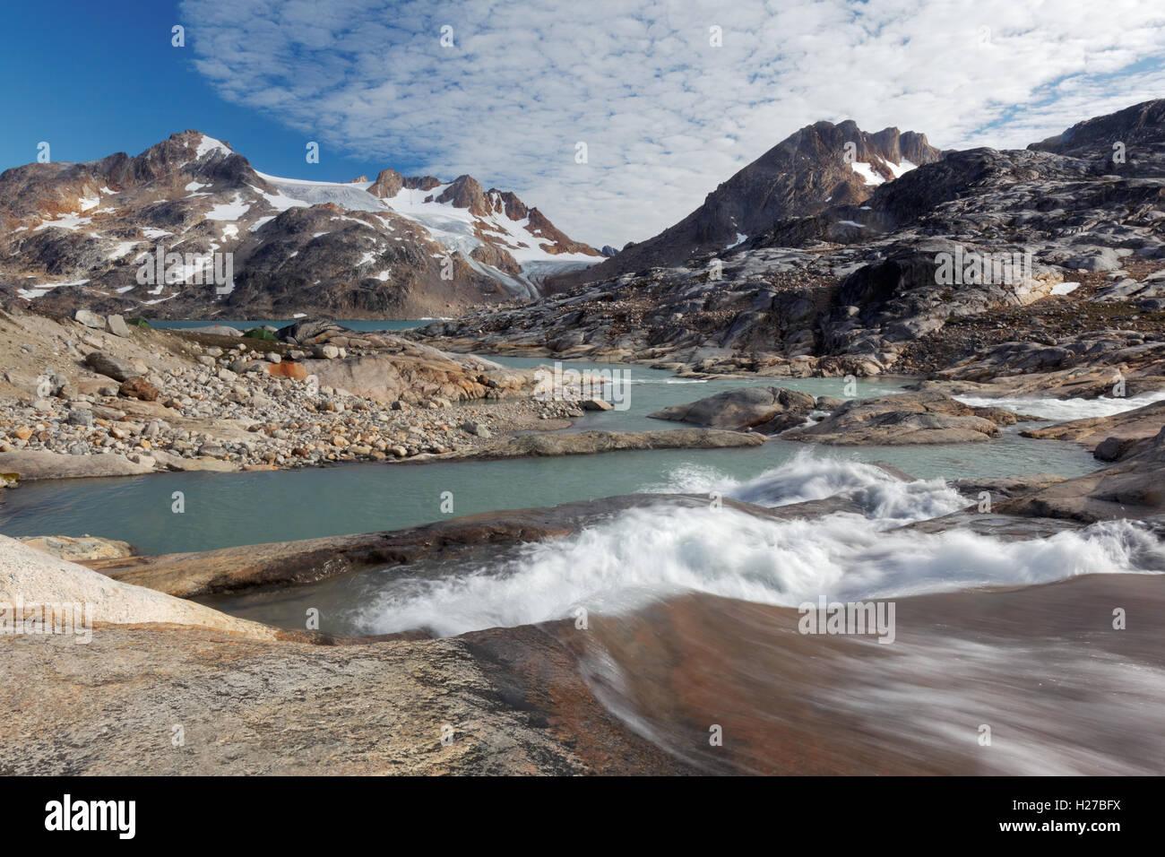 Glacial melt river and mountains, Sammileq Fjord, Ammassalik Island, East Greenland - Stock Image
