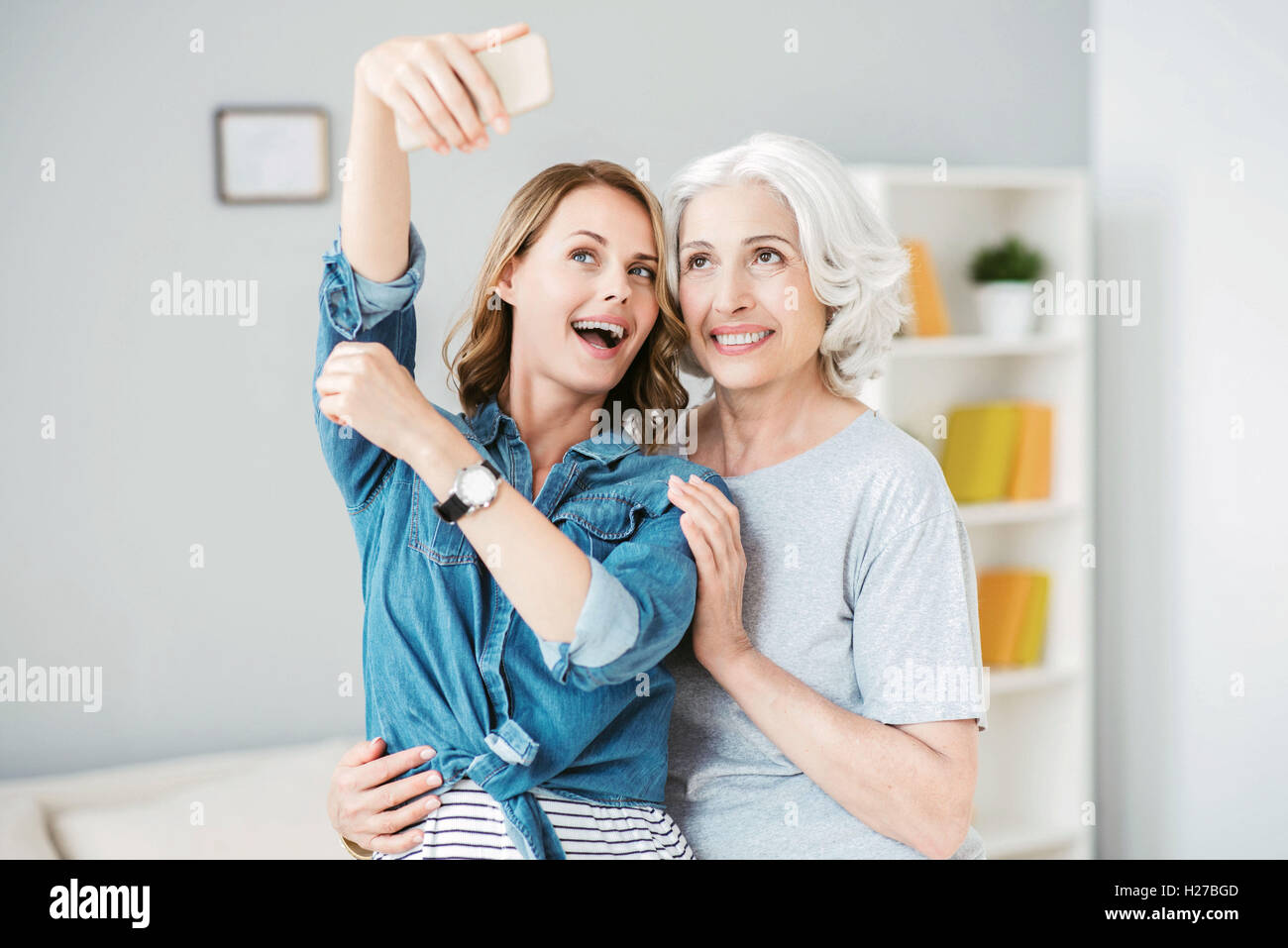 Positive woman making selfies with her mother - Stock Image