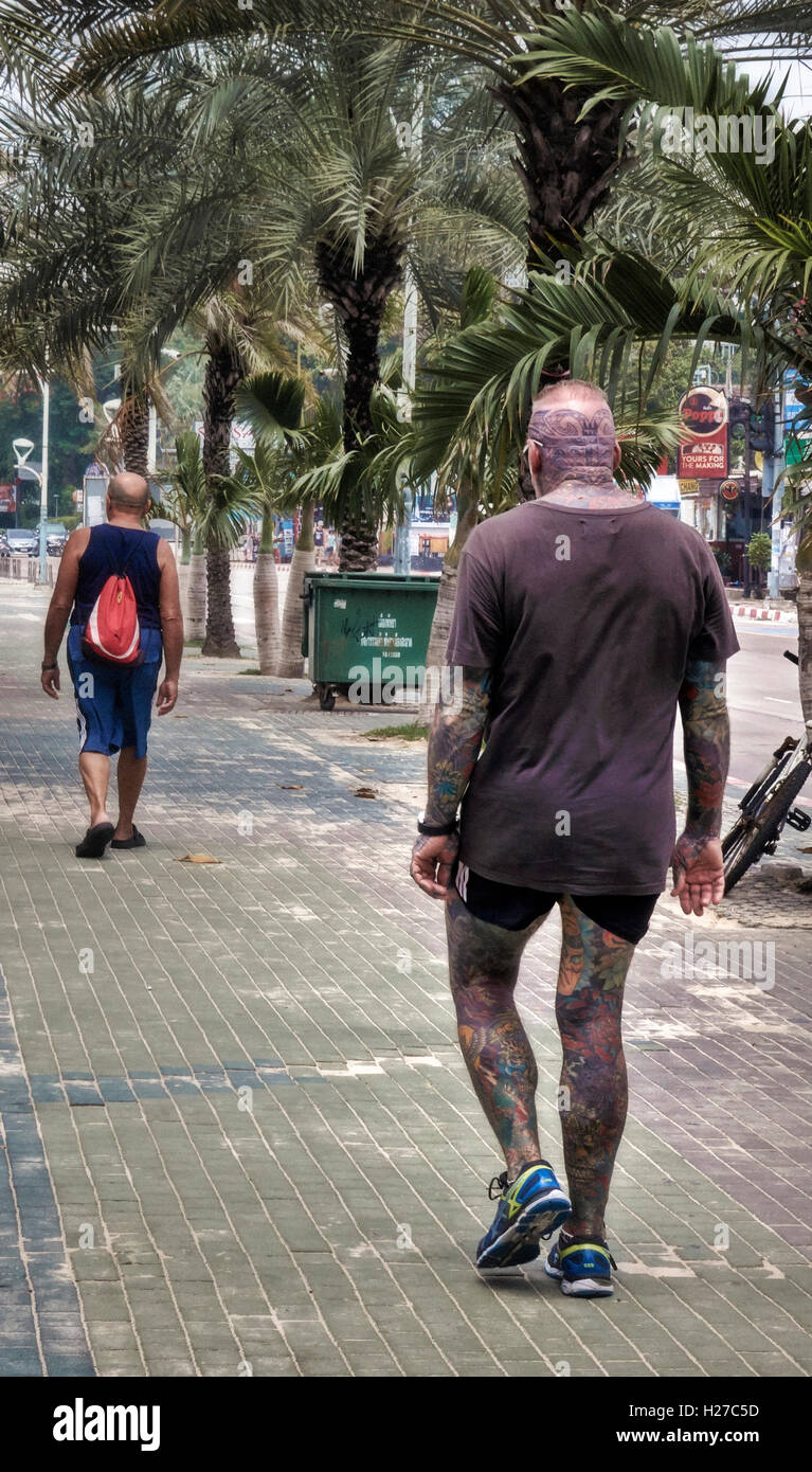 Heavily tattooed man creating an ominous situation following a lone walker. - Stock Image