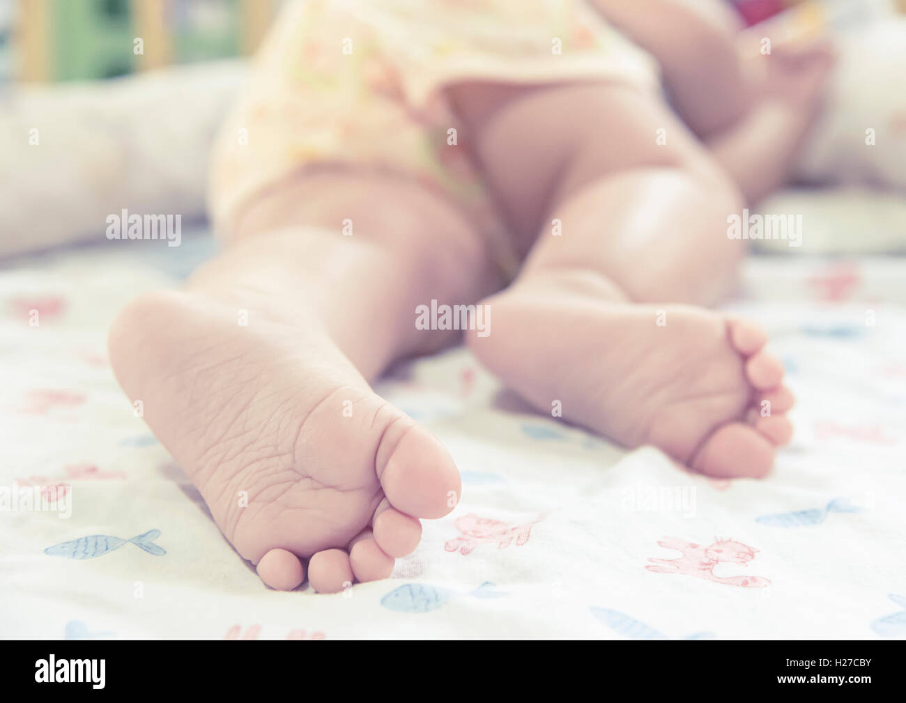 close up baby feet while sleeping on the bed - Stock Image