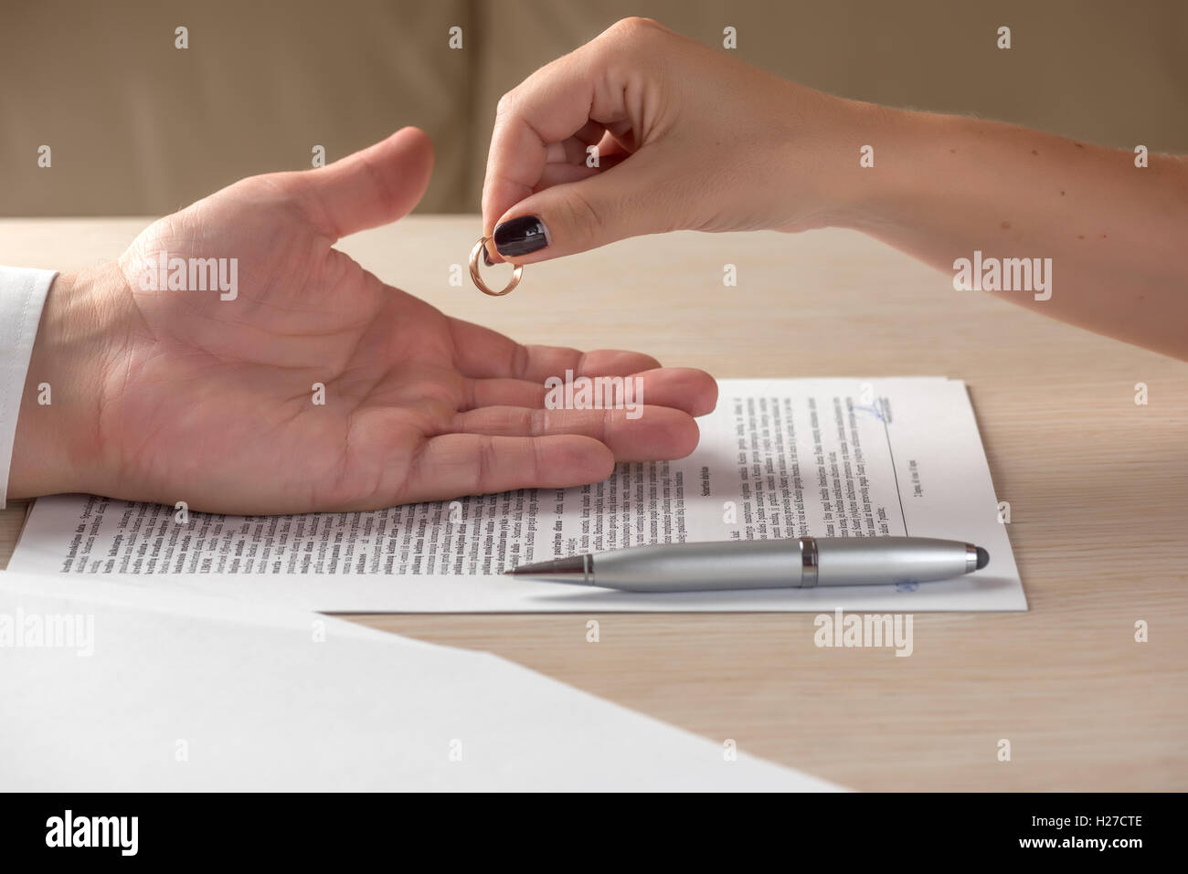 Wife and husband signing divorce documents, woman returning wedding ring - Stock Image