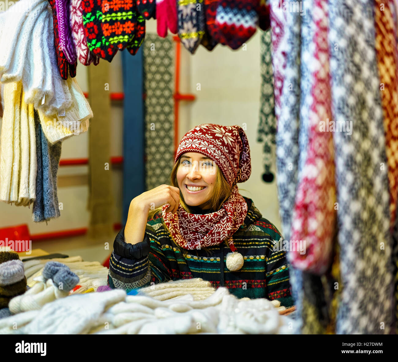 Riga, Latvia - December 24, 2015: Young woman festively dressed pictured while trading with various warm clothes - Stock Image